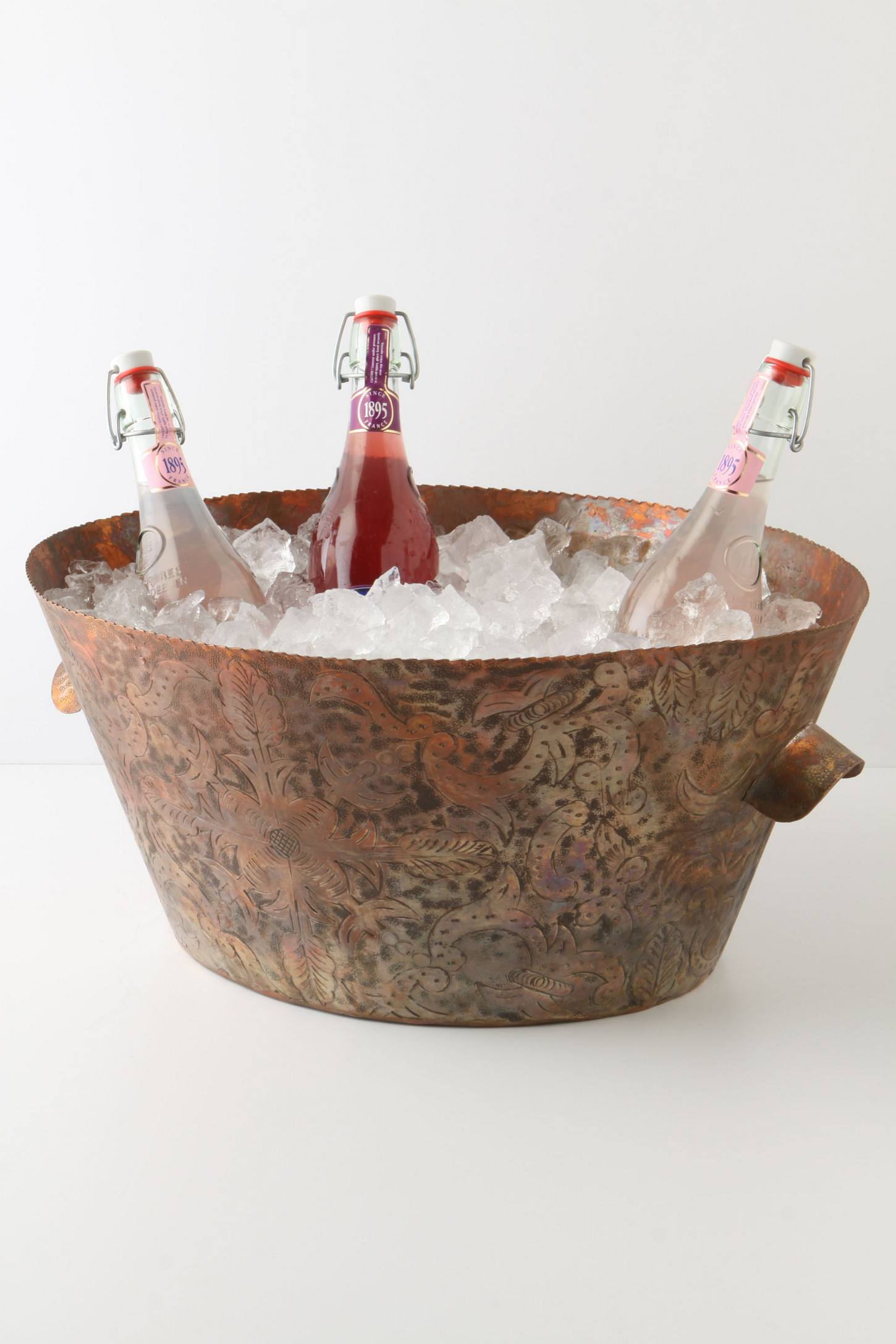 Copper party bucket with ice and three bottles in it