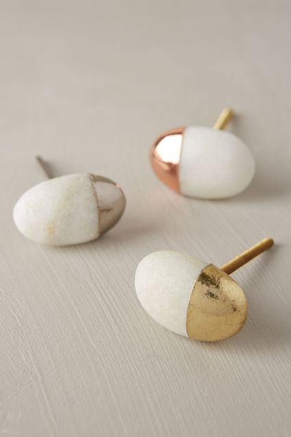 Gulddoppade stenknoppar lyfter en enkel byrå i trä.