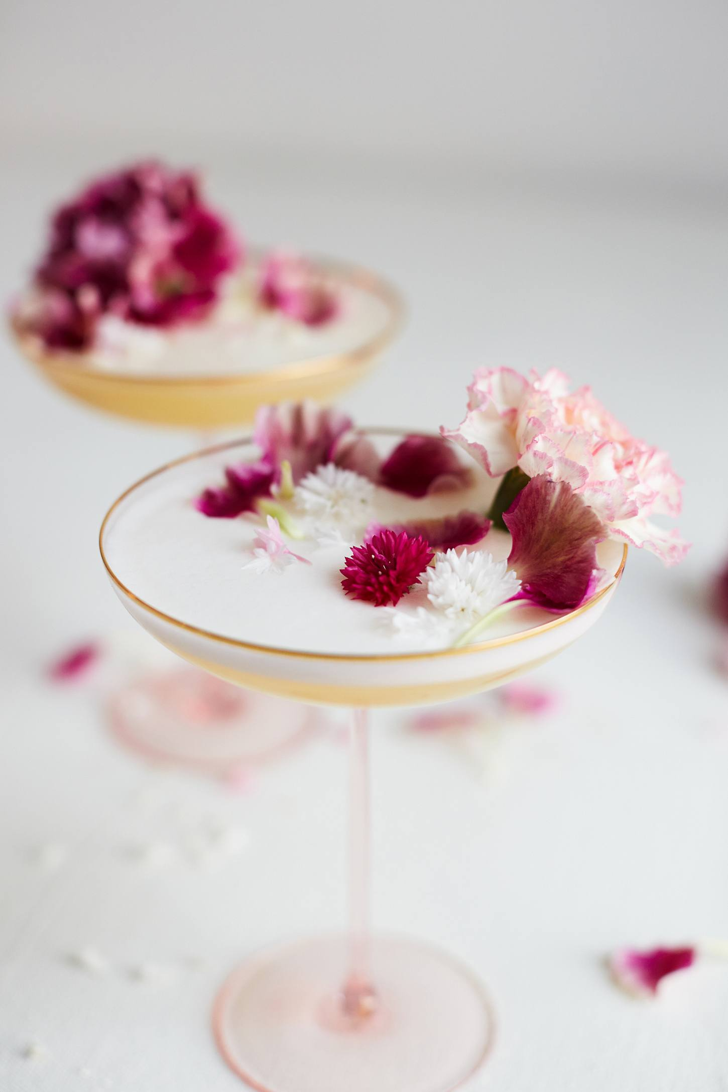 Image of Anthropoligie's Gilded Rim Coupe with flowers and champagne